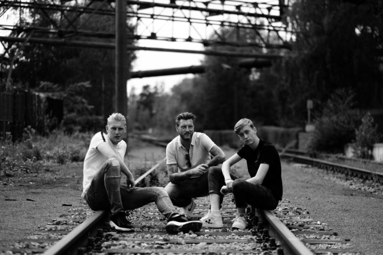 A dad and his sons sitting on train tracks at Landschaftspark Duisburg