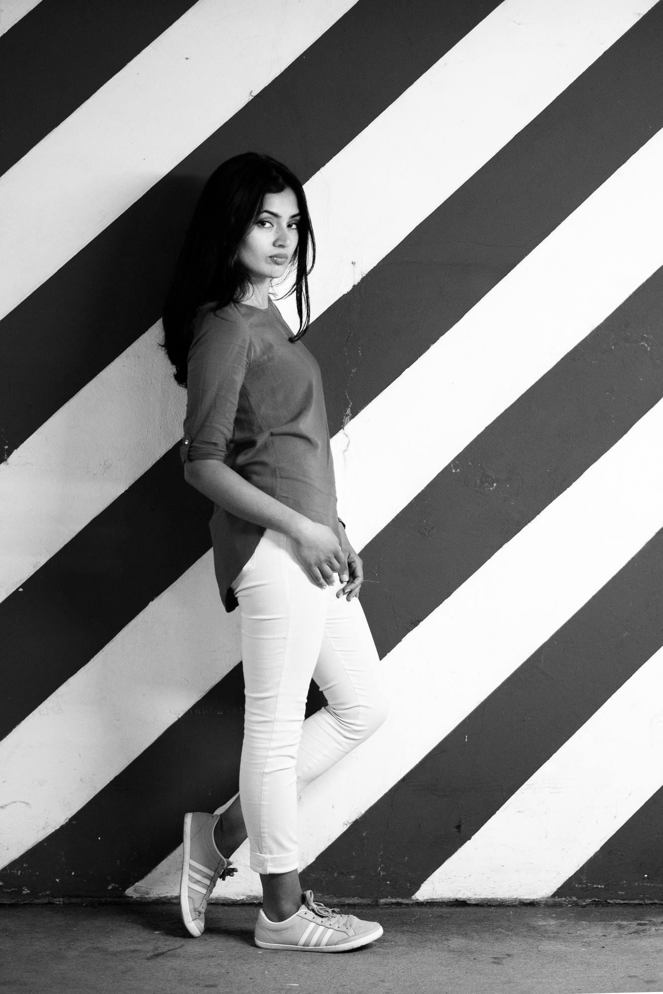 A girl with a red shirt and white pants in front of a red and white striped background