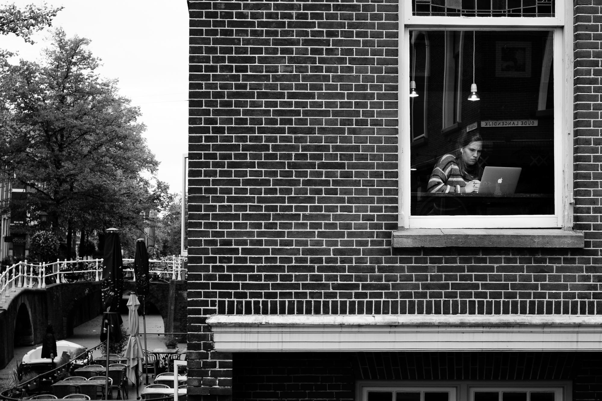 A girl working on her Macbook behind a window in Delft, the Netherlands