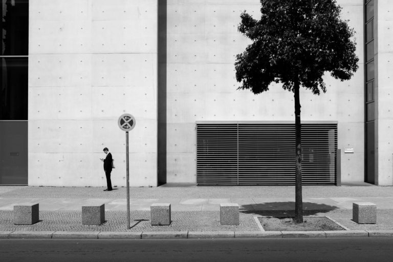 A Businessman looking at his cellphone at Regierungsviertel, Berlin, Germany
