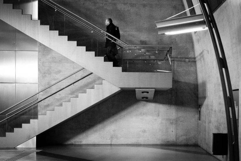A man walking up the stairs in a subway station in Cologne, Germany