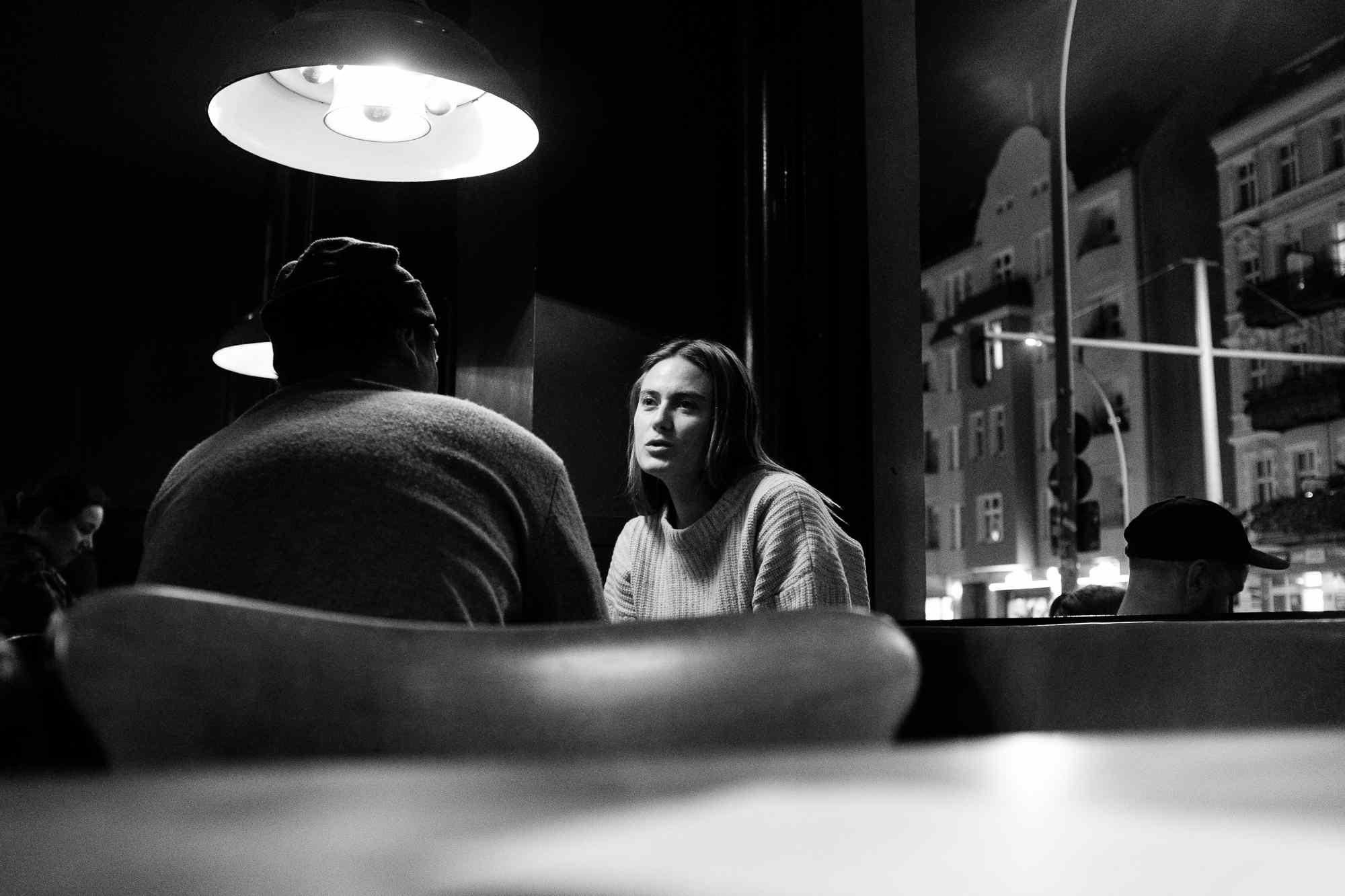 A boy and a girl in conversation in a dark bar in Berlin, Germany