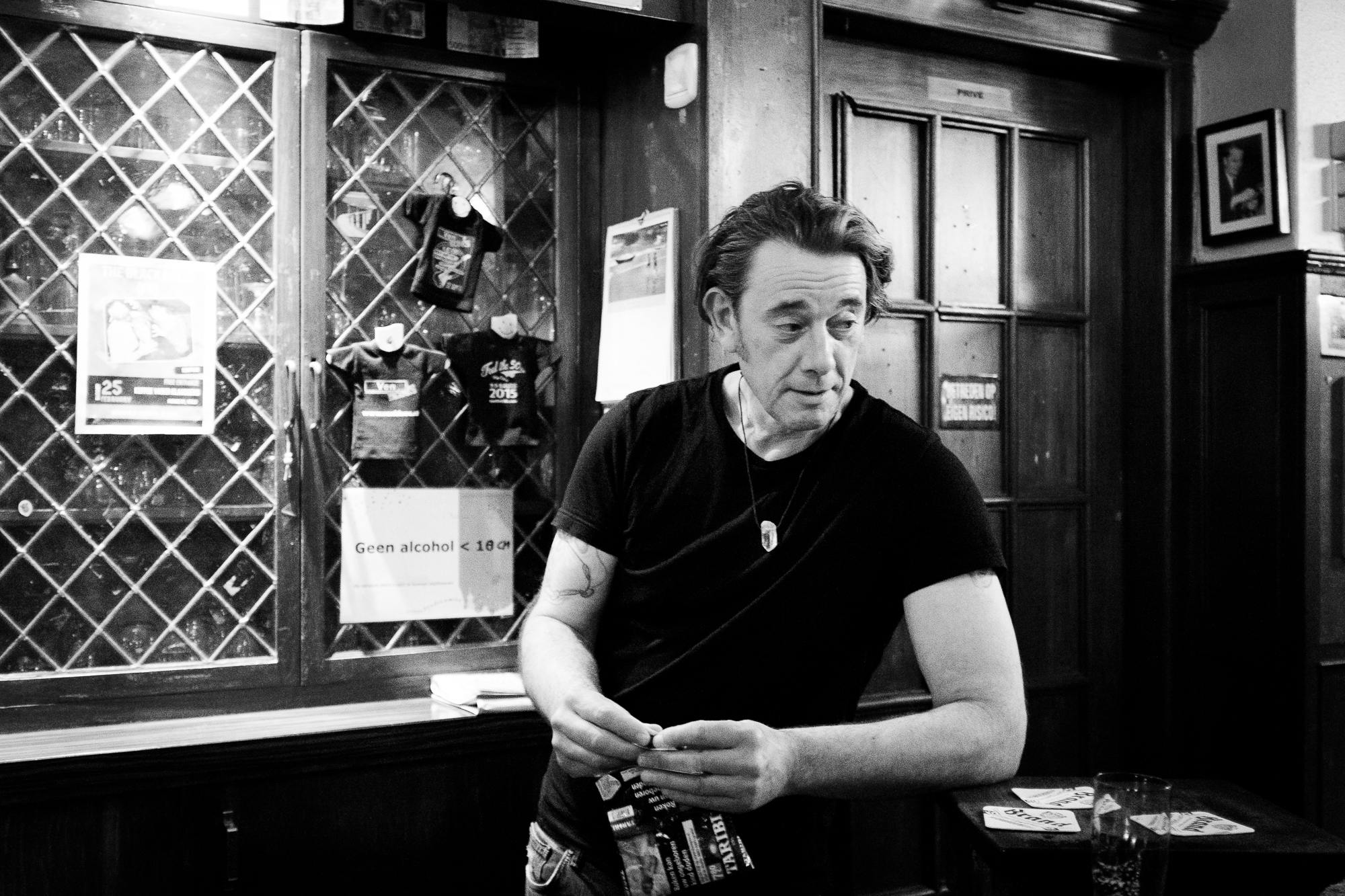 Bartender rolling a cigarette while in conversation