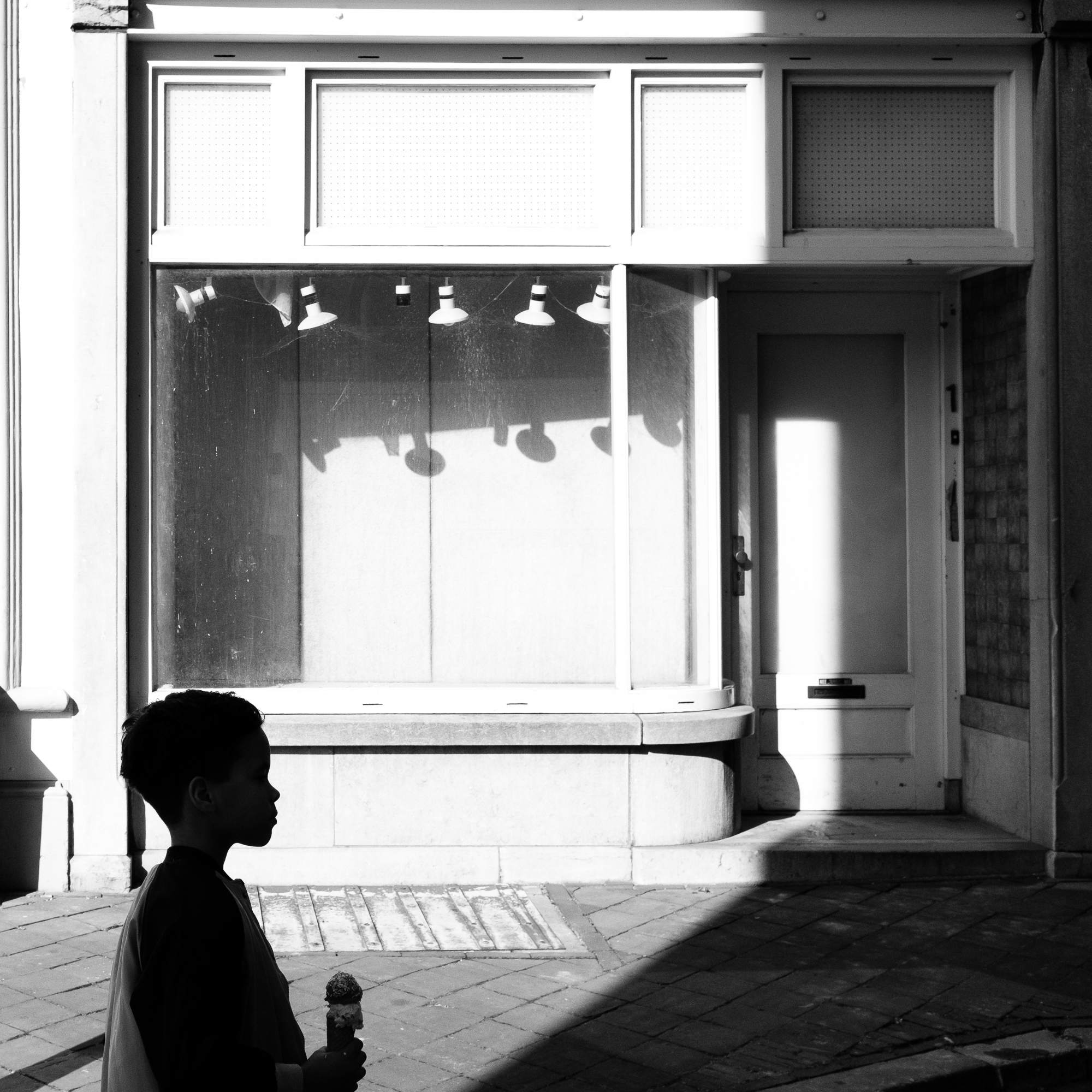An empty store window with a sihouette of a kid with an icecream