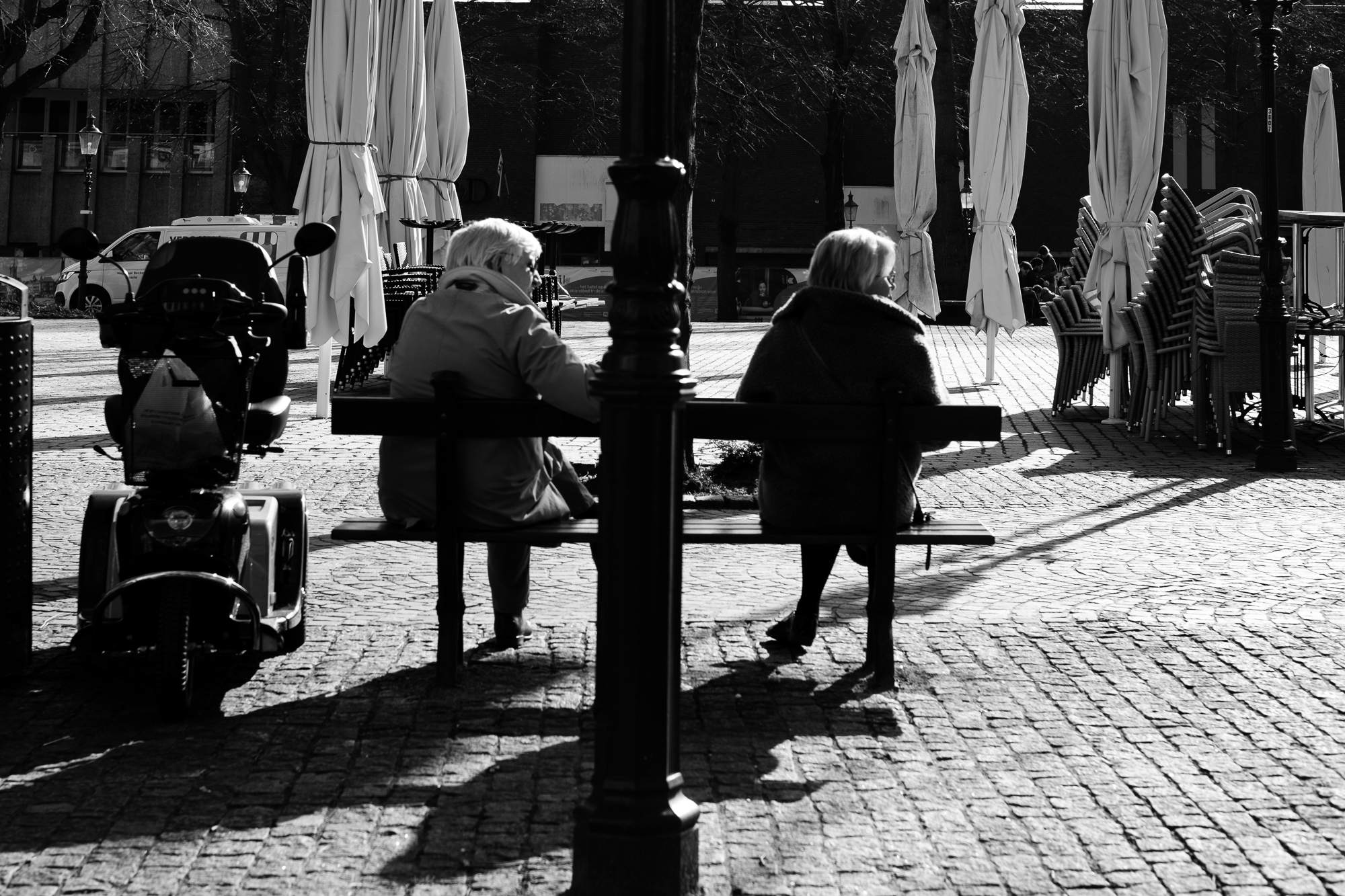 Two ladies sitting on a park bench looking to the right