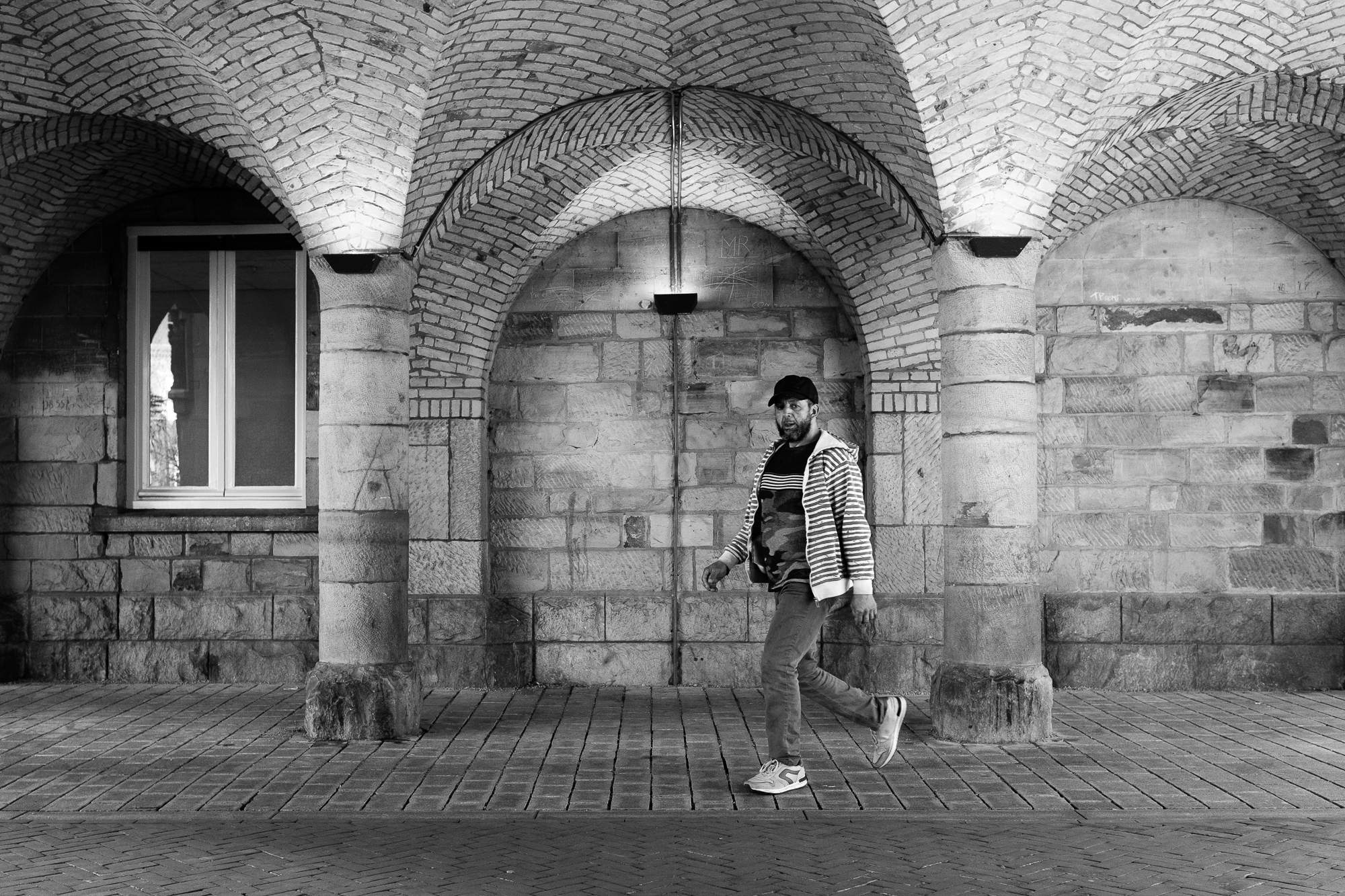 A man walkung through an overpass with arches in Roermond