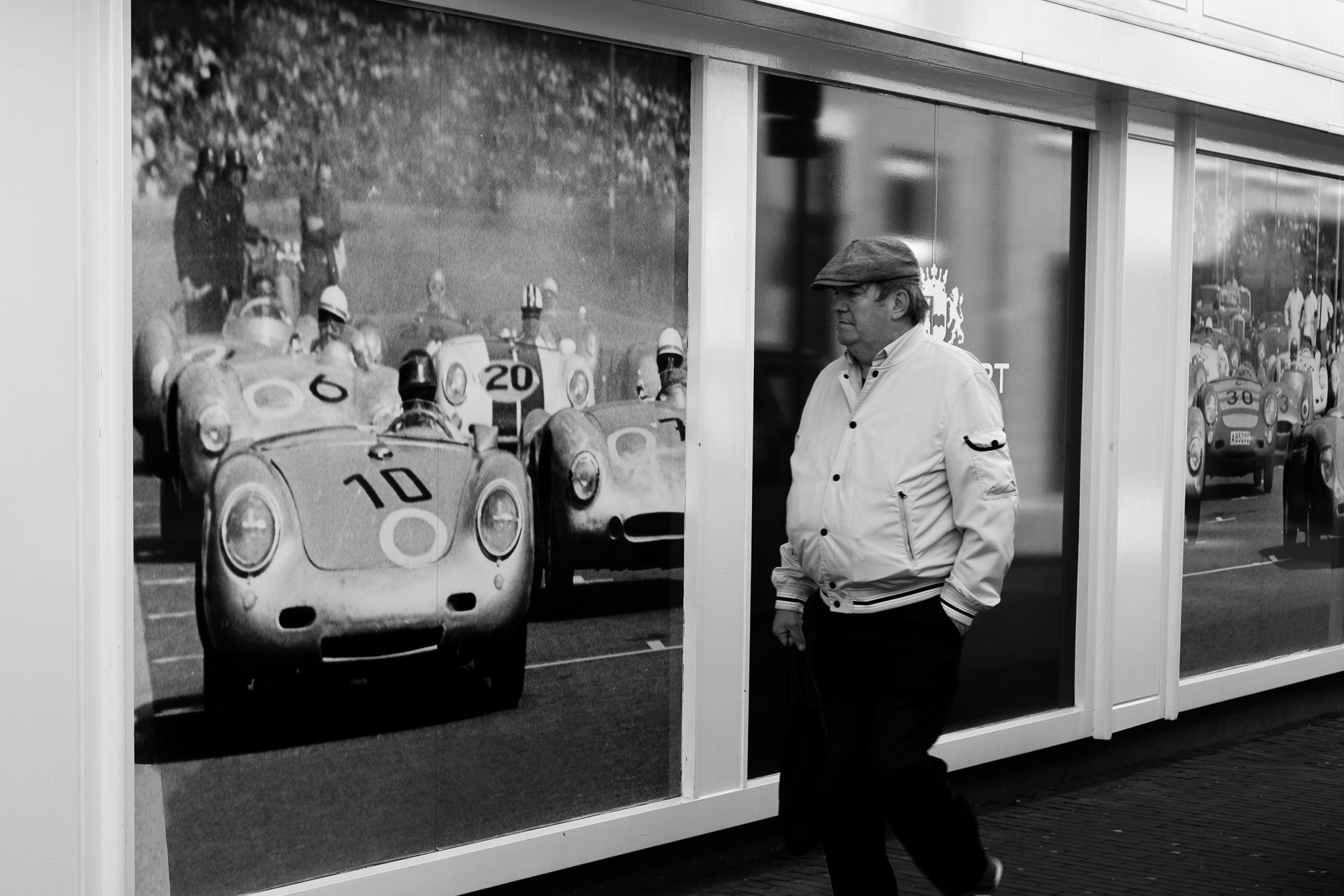 A man walking by a window with a big photo of classic race cars