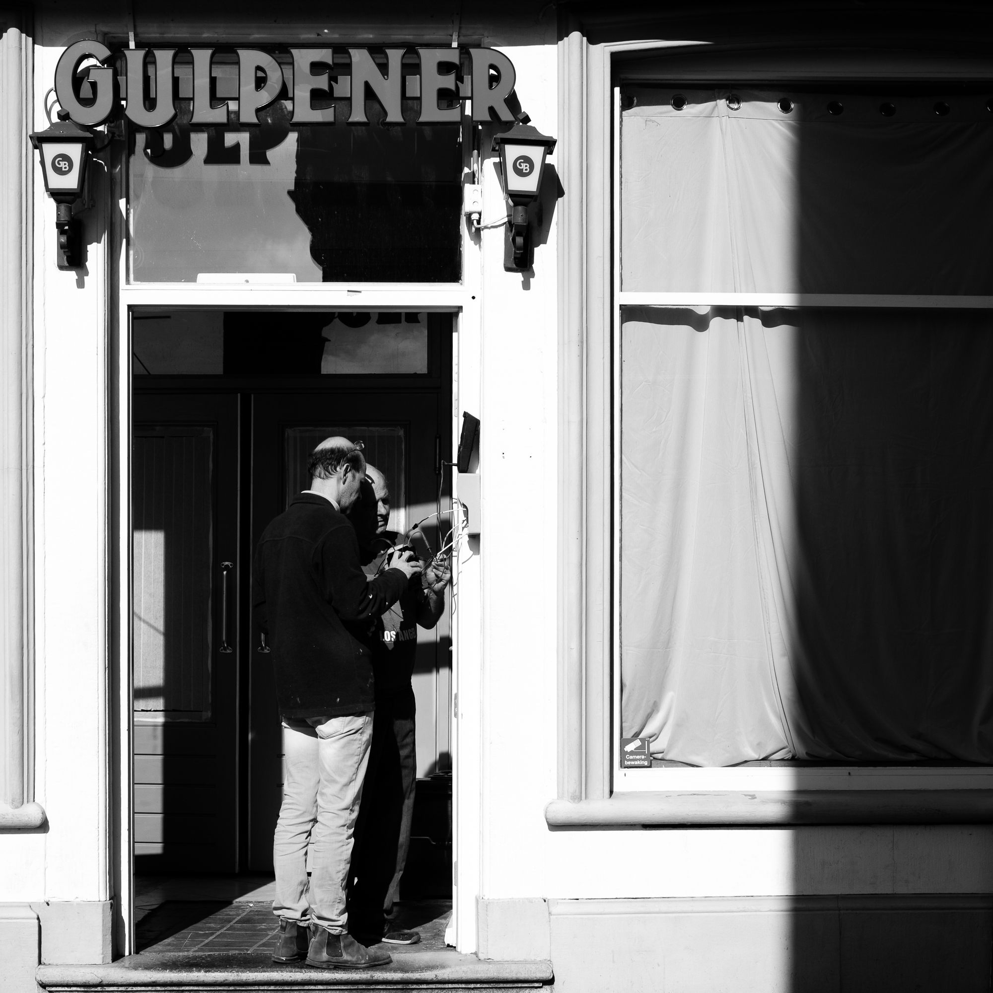 Two men working on electricity at a bar with a Gulperner sign