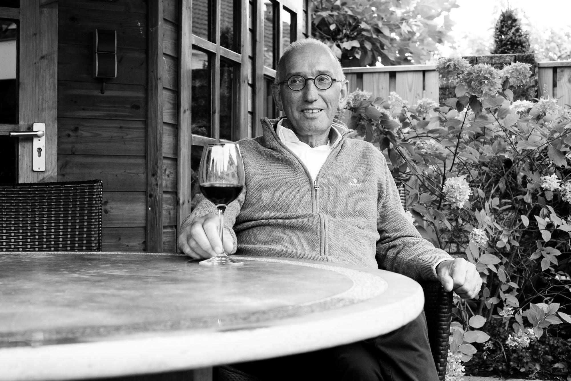 A man in his garden, enjoying a glass of wine