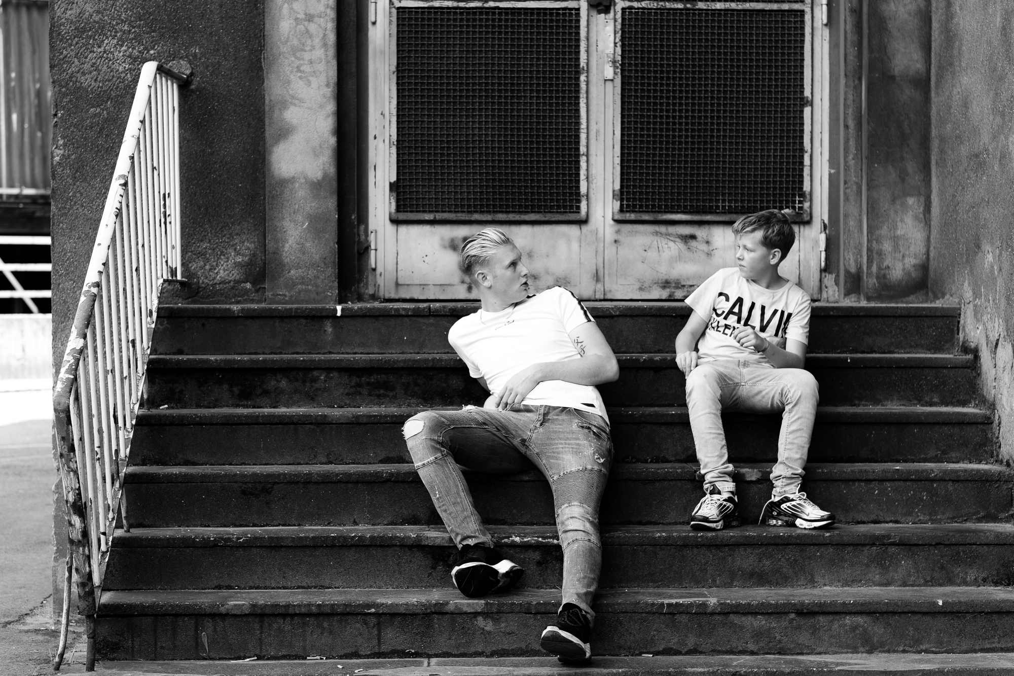 two boys looking at each other on stairs