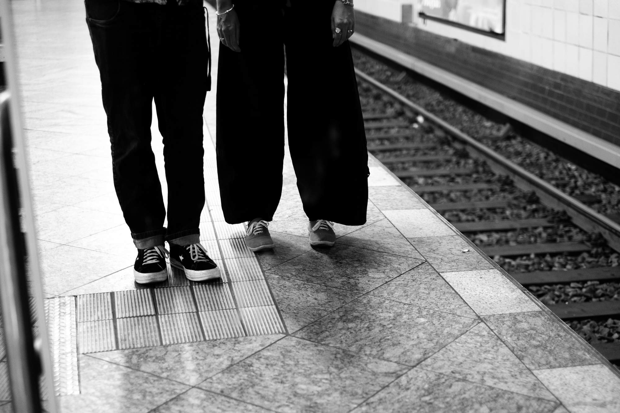 Two pairs of legs on a subway platform in Berlin