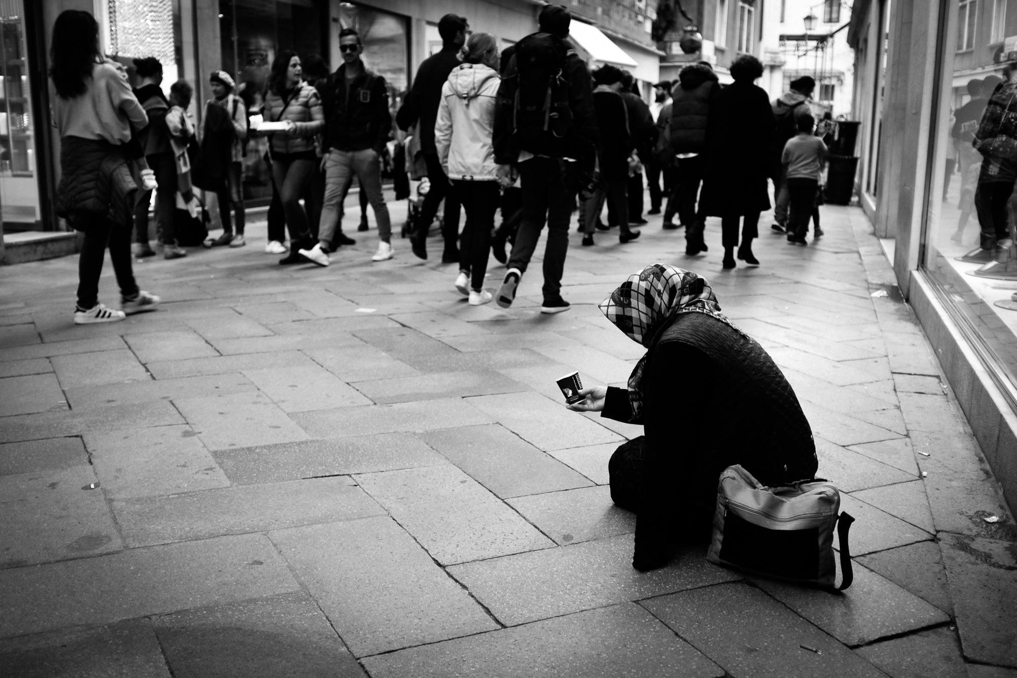 Street scene of a beggar among shoppers in Venice